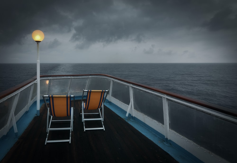 two brown and white folding chairs on boat surrounded by body of water under gray sky
