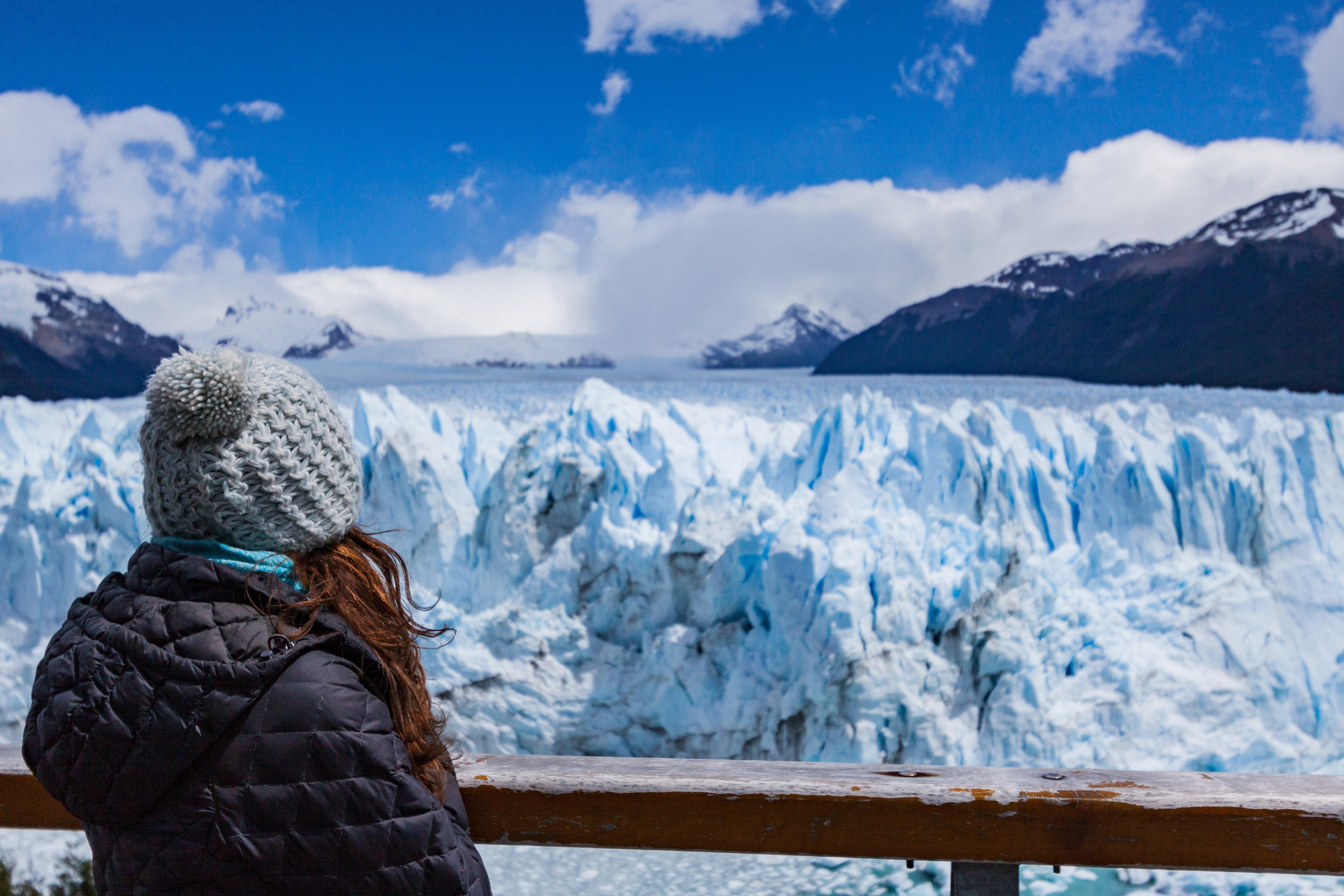 person wearing black hooded jacket seeing snow mountain during daytime