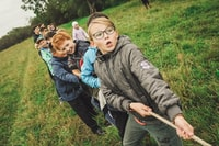 group of children pulling brown rope