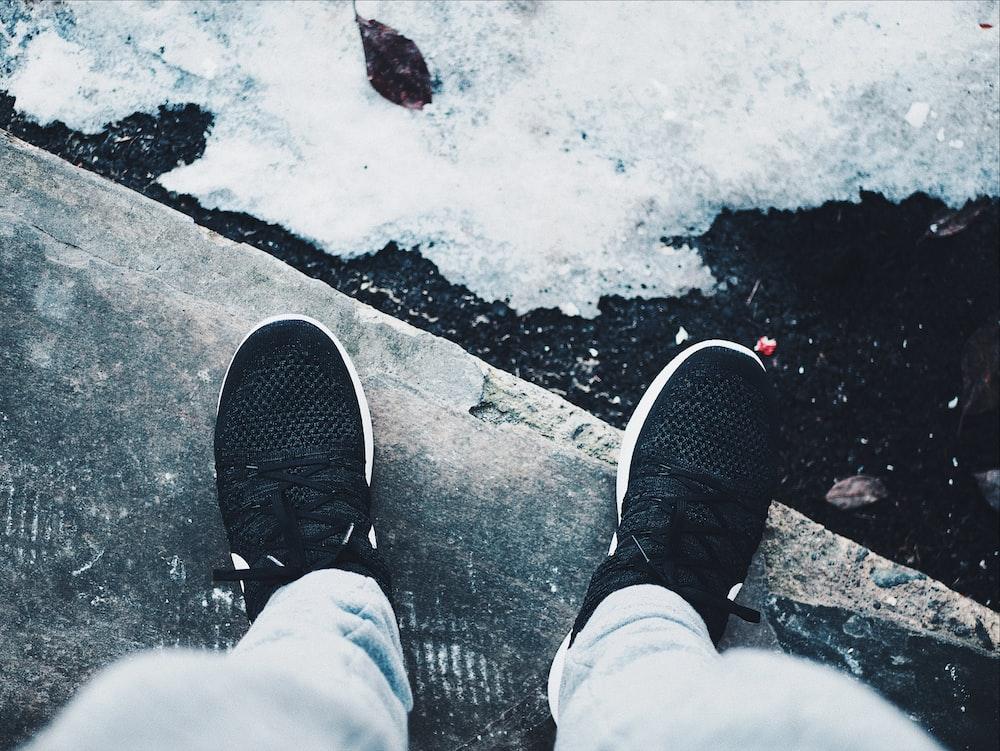 person wearing black Nike sneakers standing beside snow