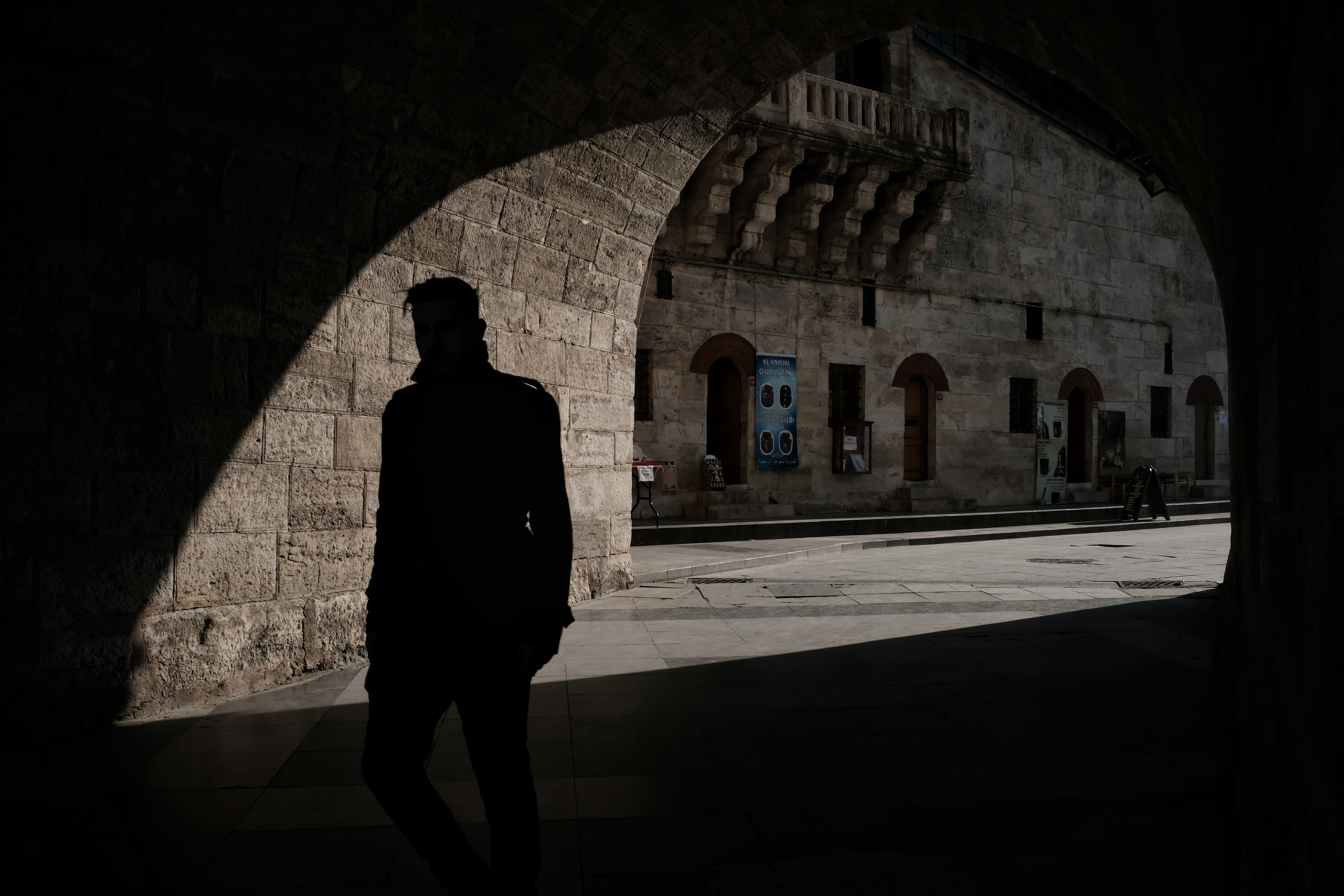silhouette of man inside of tunnel during daytime