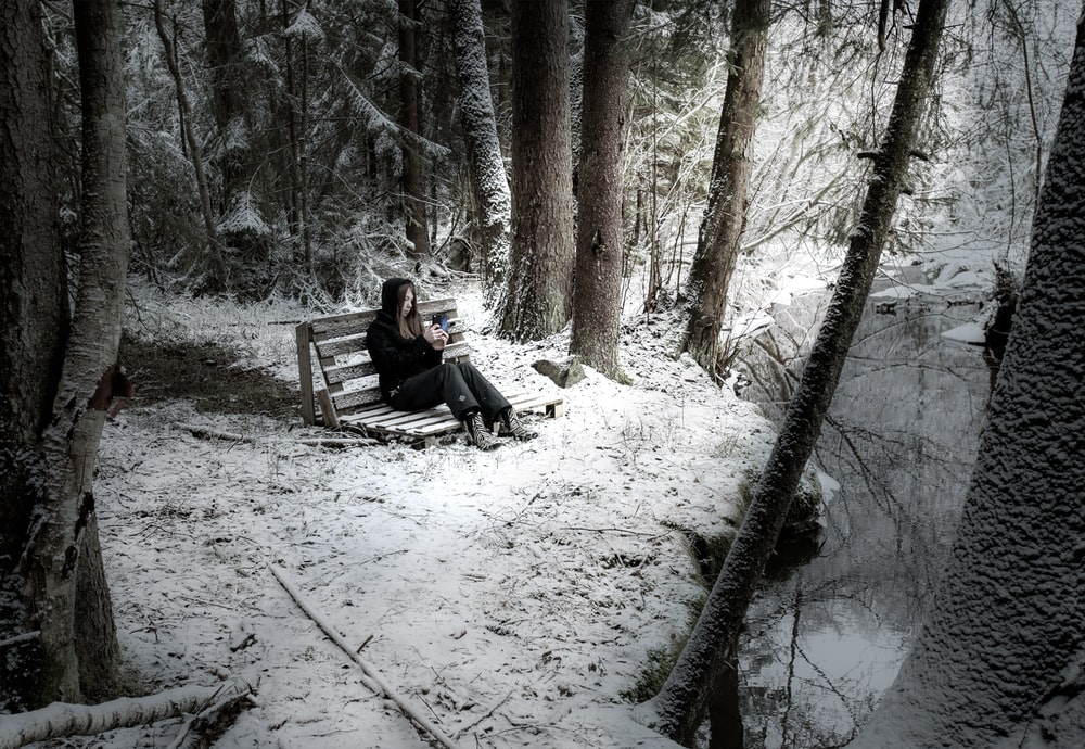 woman wearing black denim jeans sitting on bench surrounded by trees and covered with snow near body of water