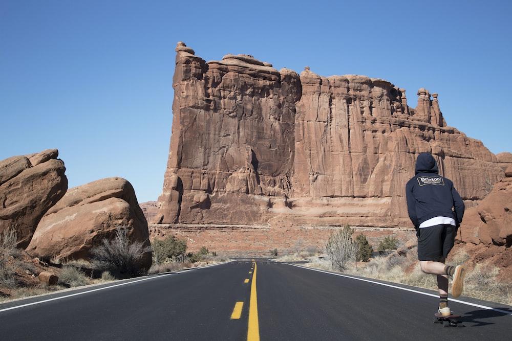 person in blue hoodie skateboarding near ruins