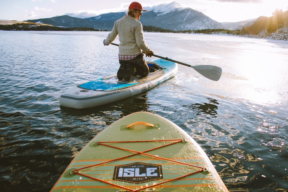 man wearing gray sweater kneeding on paddle board with holding oar during daytime