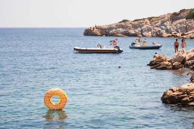 group of people swimming on body of water during daytime mediterranean teams background