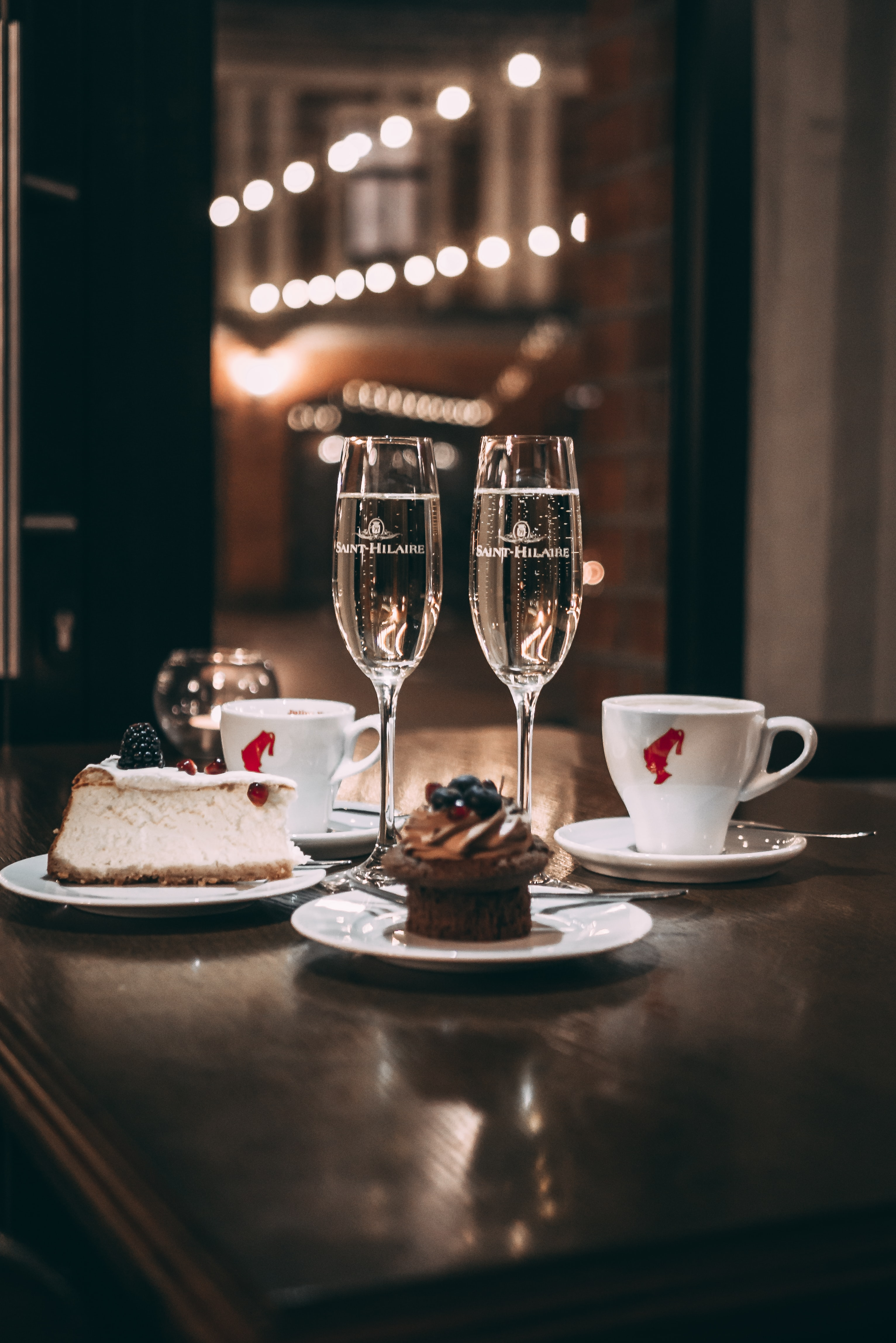 two champagne flute glass beside sliced cake and cupcake