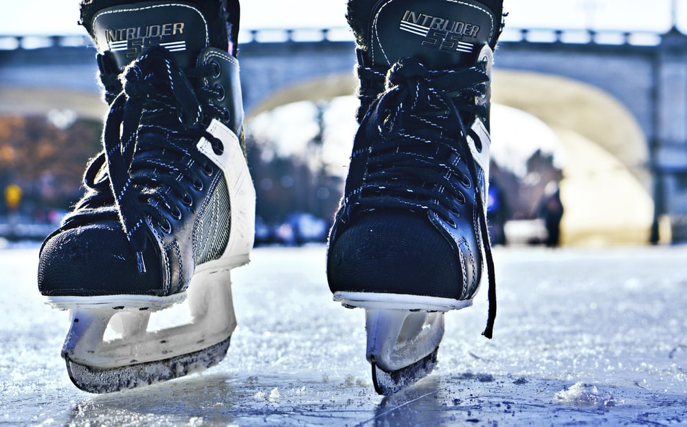 close-up photo of black-and-gray Intruder ice skates on frozen body of water
