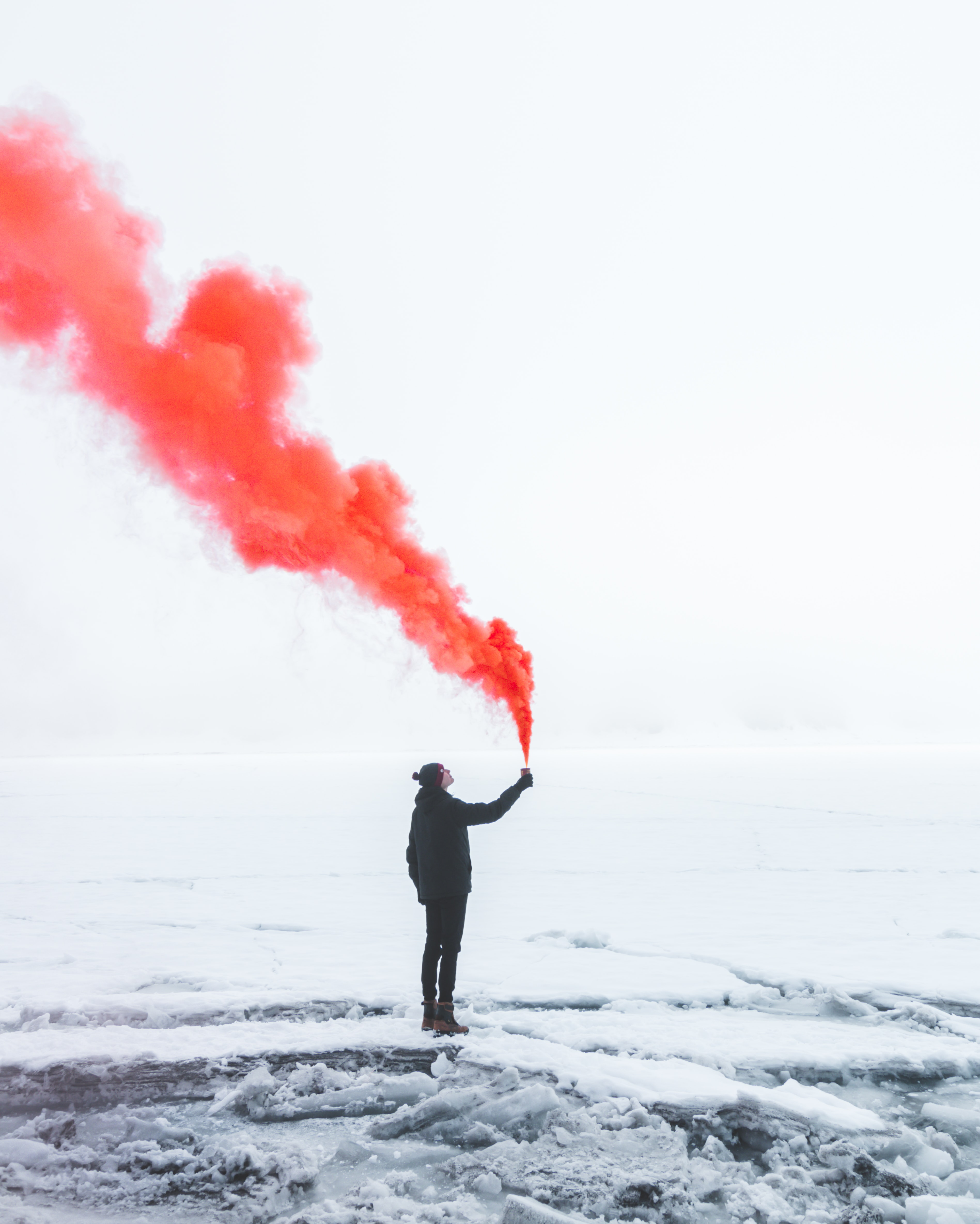 person wearing black jacket and holding red colored smoke flare during daytime