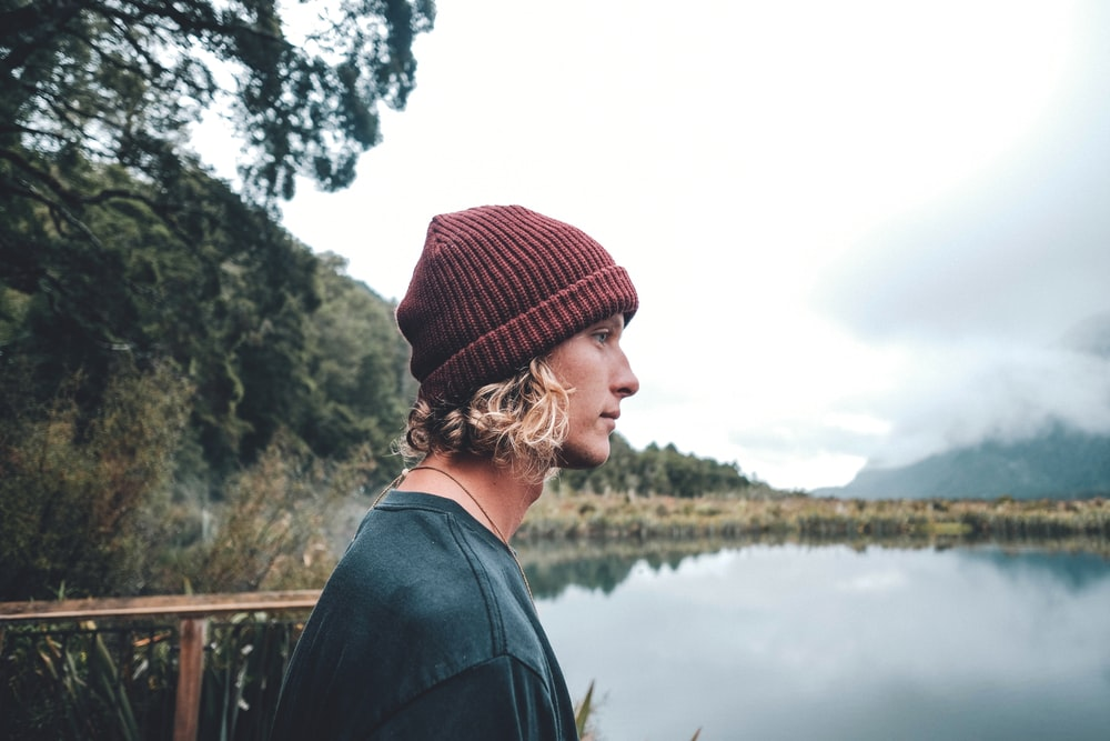 man wearing maroon knit hat standing in front of body of water during daytime