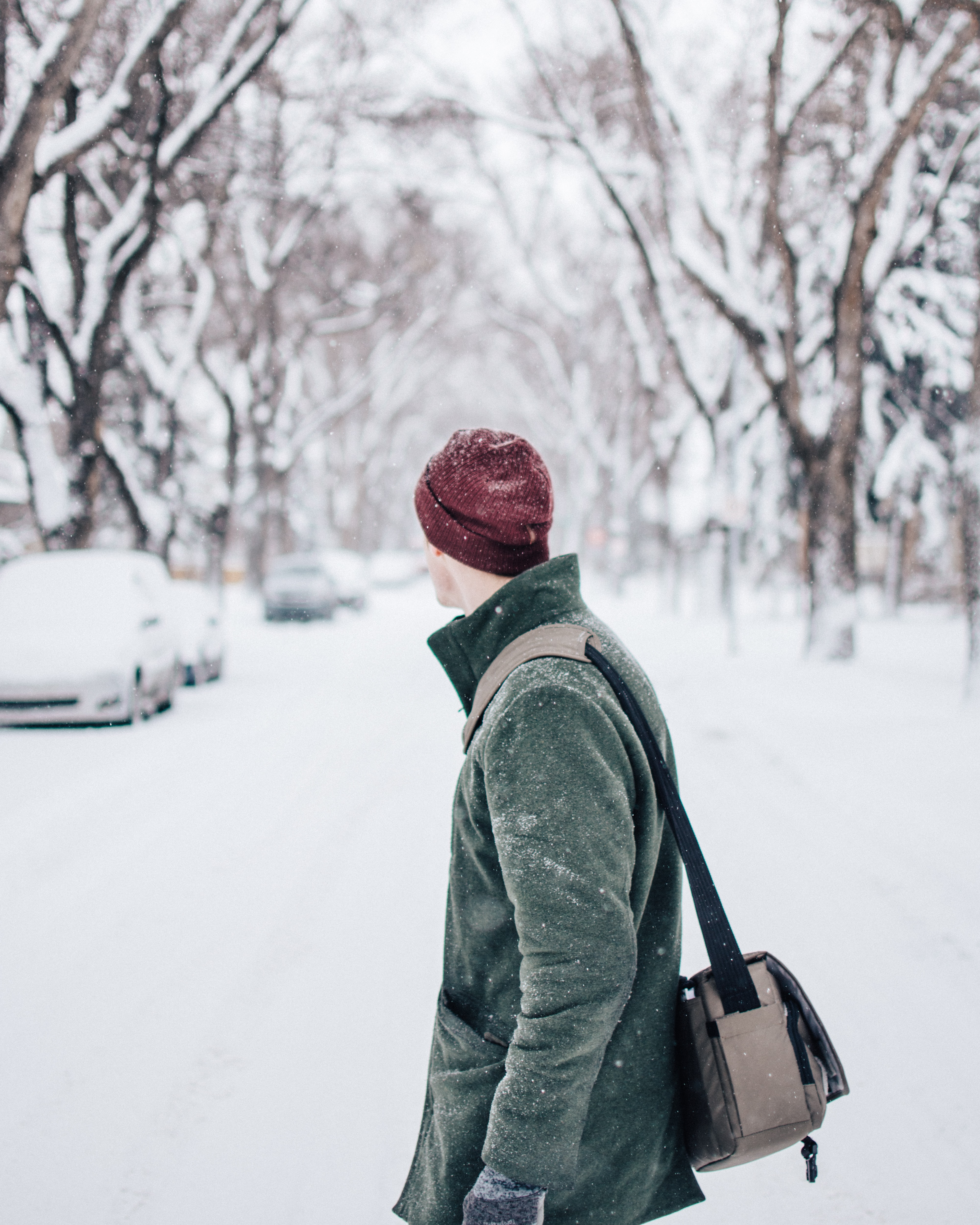 selective focus photography of man wearing coat and beanie standing watching vehicle on road