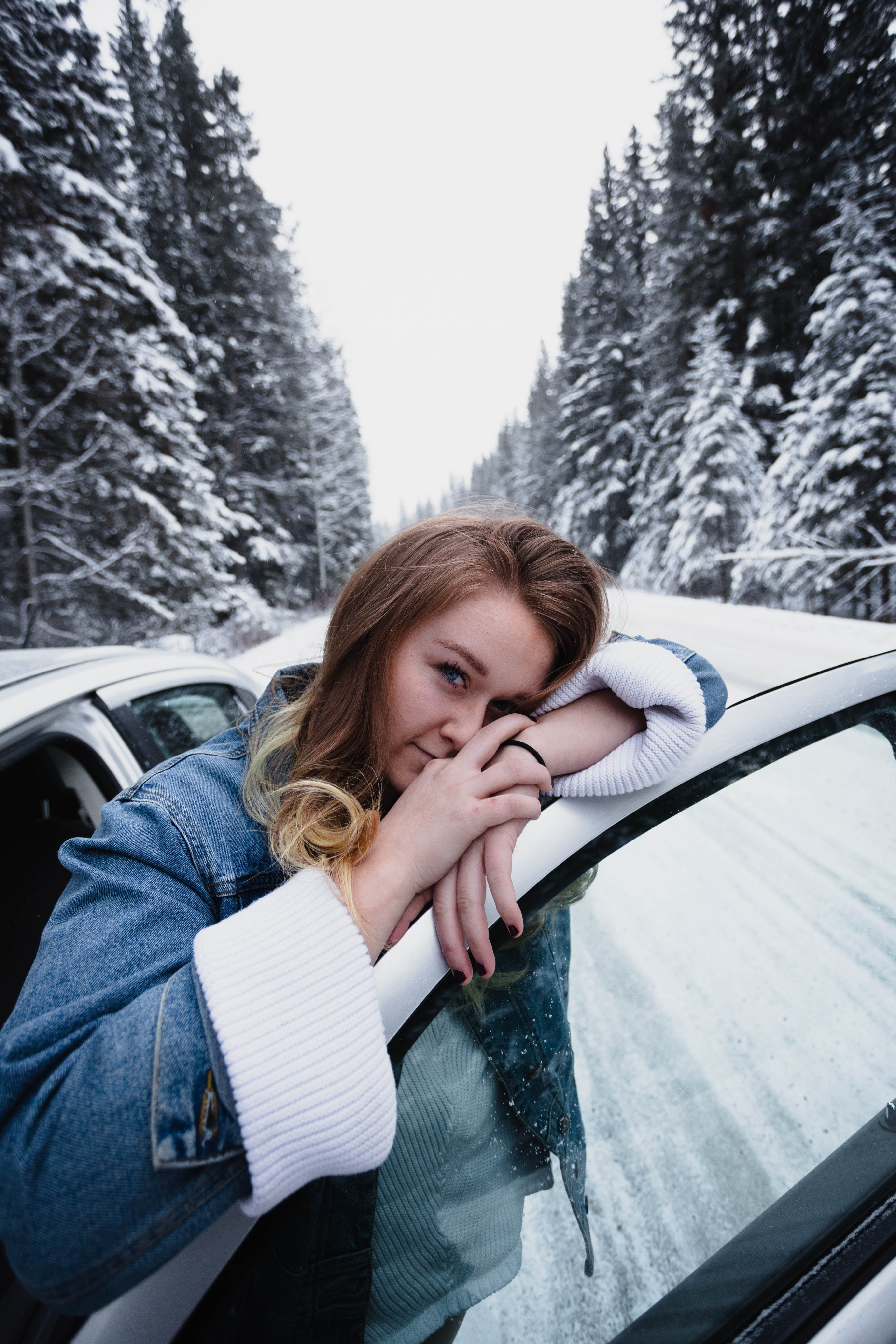 woman wearing blue denim jeans leaning on white vehicle door on road beside pine trees covered with snow during winter