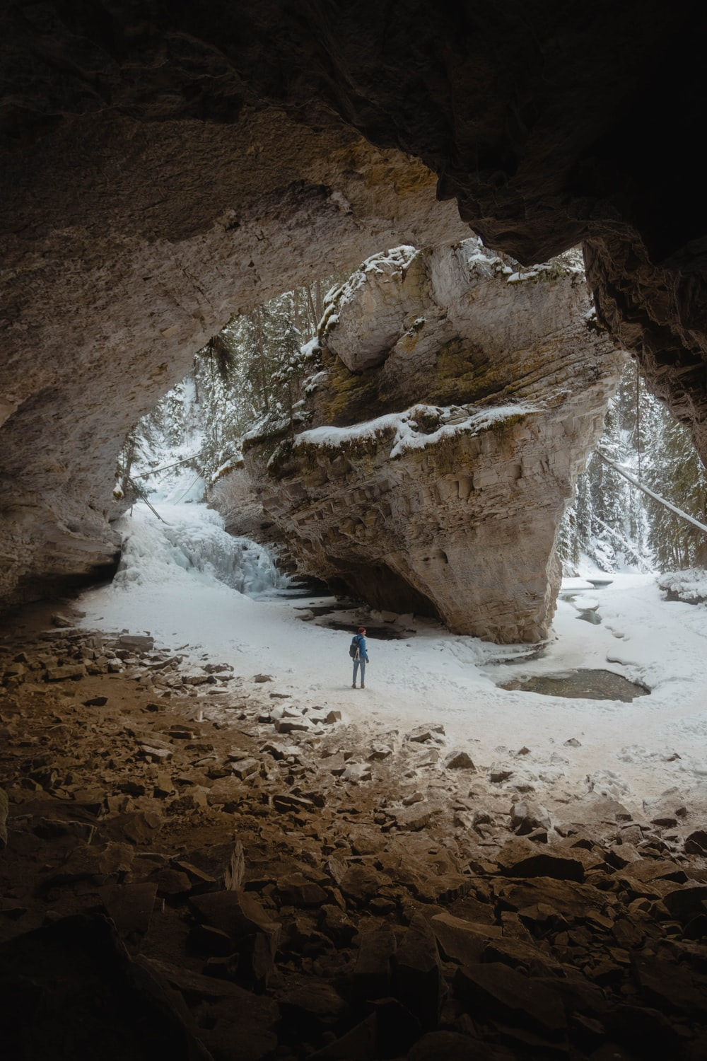 person standing between large rock formation filled with snow