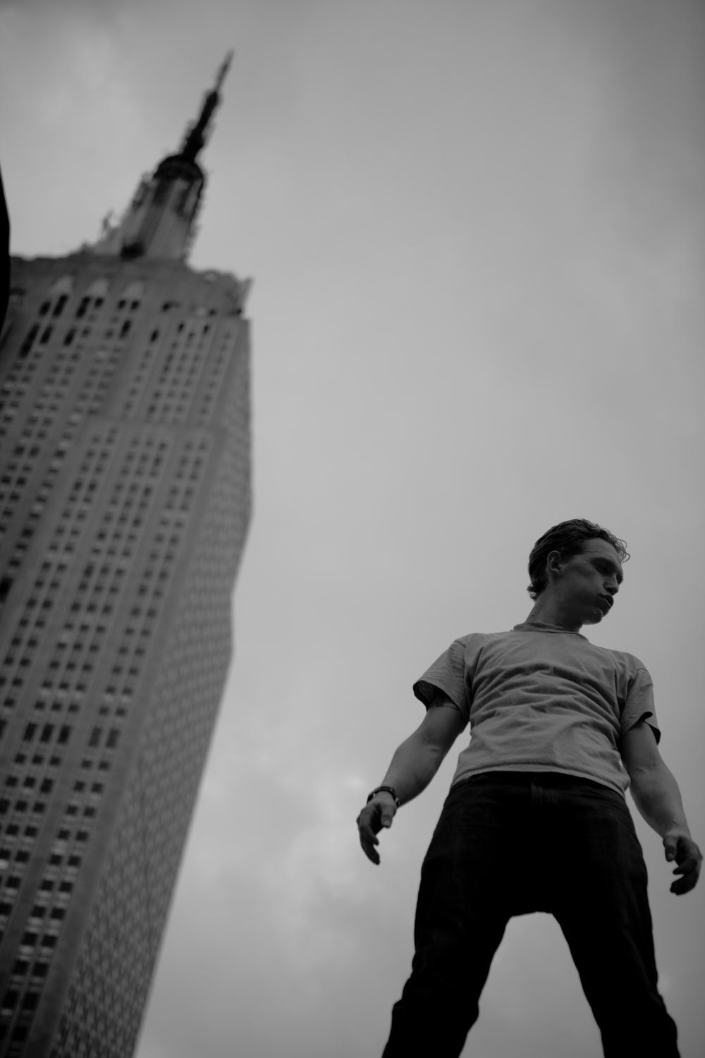 grayscale low-angle photo of man standing near building