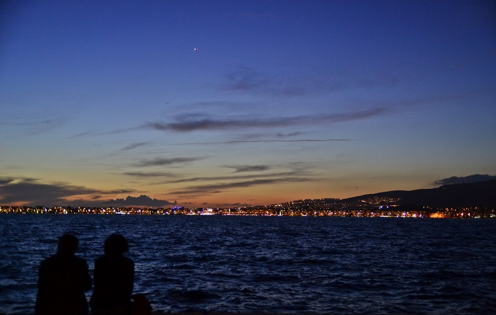 couple sitting near body of water watch city lights