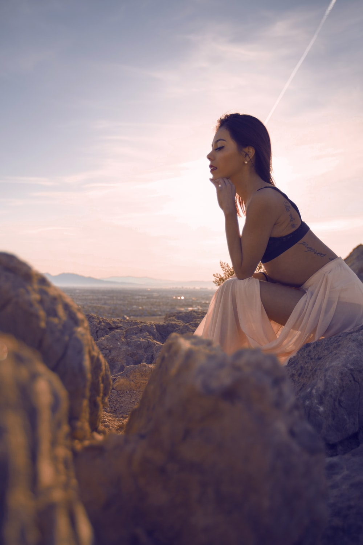 woman sitting on grey rock under blue sky