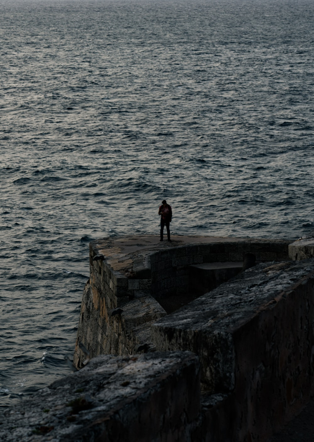 man standing on cliff near the bodies of water