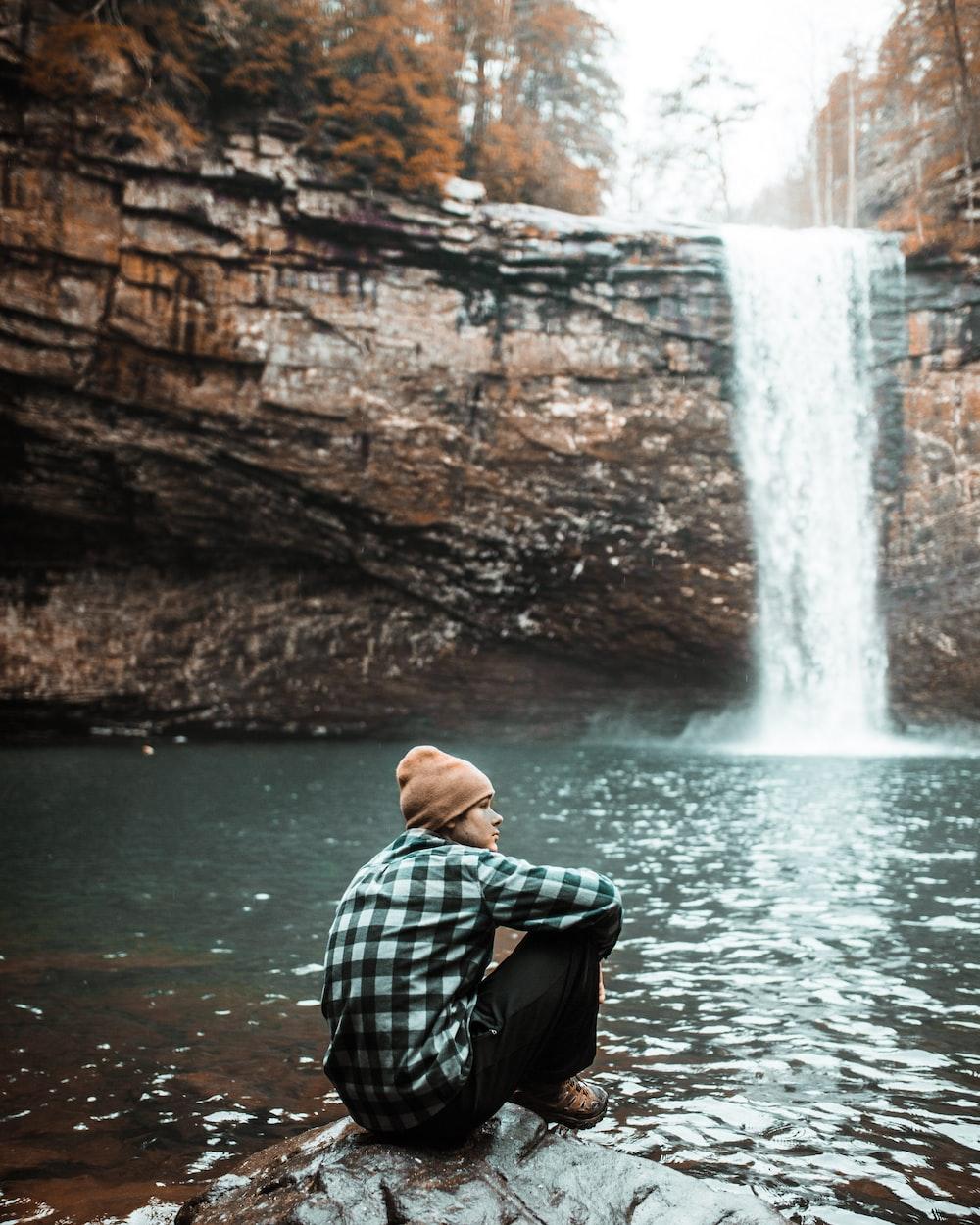 man sitting on brown stone near waterfall during daytime