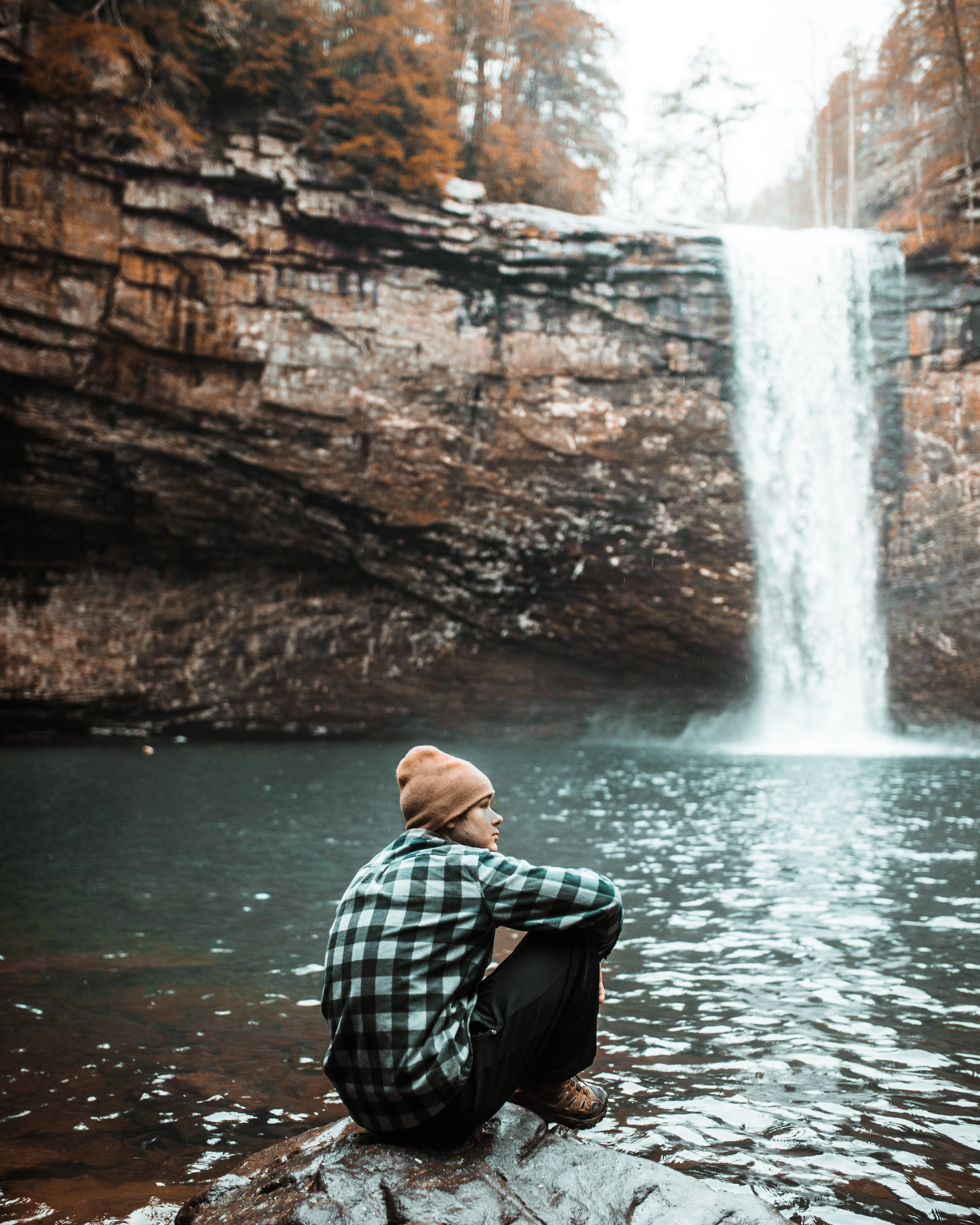 man sitting on brown stone near waterfall during daytime