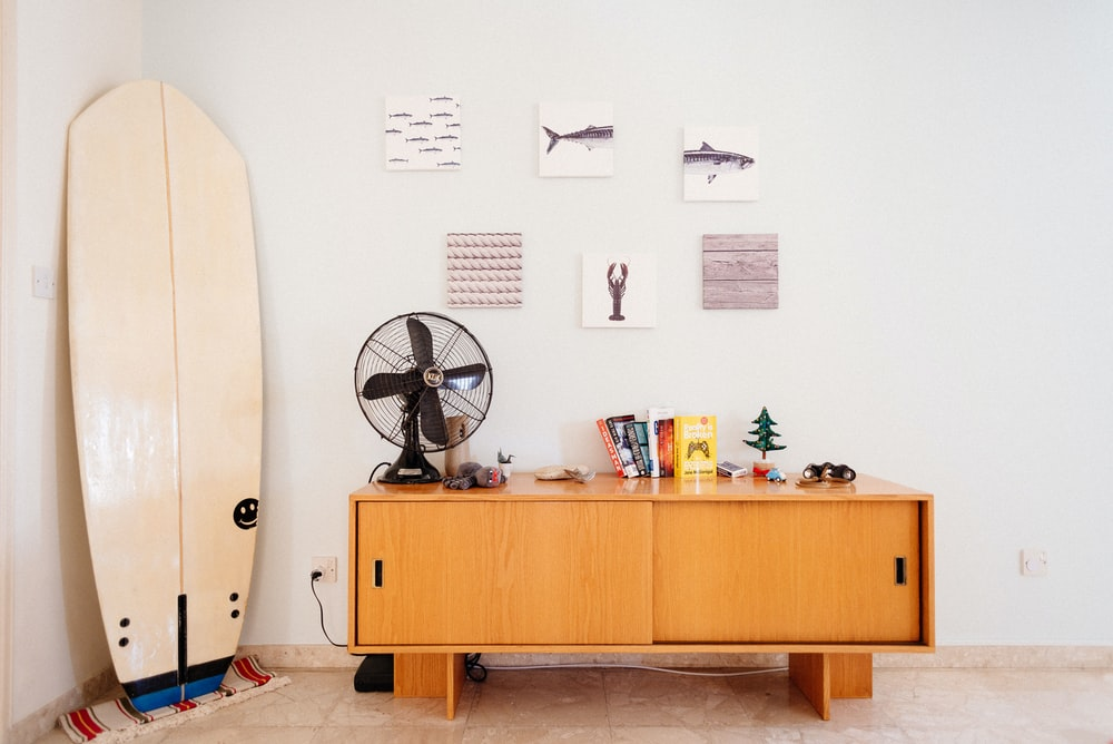 white surfboard beside brown wooden credenza