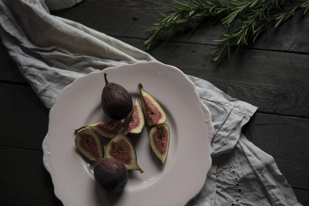 sliced fruit on plate beside green leaves