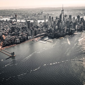 """On a recent vacation to New York, I took a """"doors off"""" helicopter flight to catch the views of the city skyline from the air. This photo was taken as we headed back to home base, and I shoved my camera out the door and pointed it back towards the city - I had no idea what I was pointing my camera too and just hoped that I got a decent photo. Needless to say I was very pleased with how this photo turned out…"""