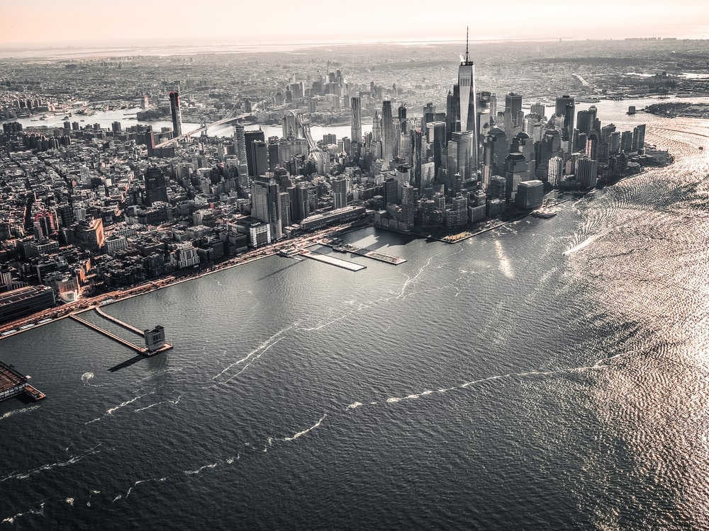 aerial photography of large body of water across city with high-rise buildings at daytime