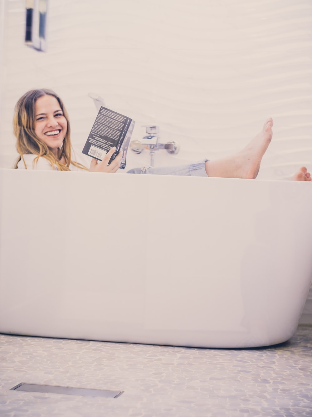 woman in bathtub holding black book while taking selfie