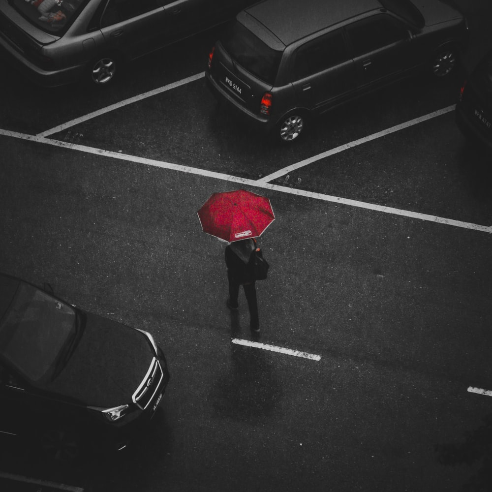 selective color photography of man using red umbrella surrounded by cars