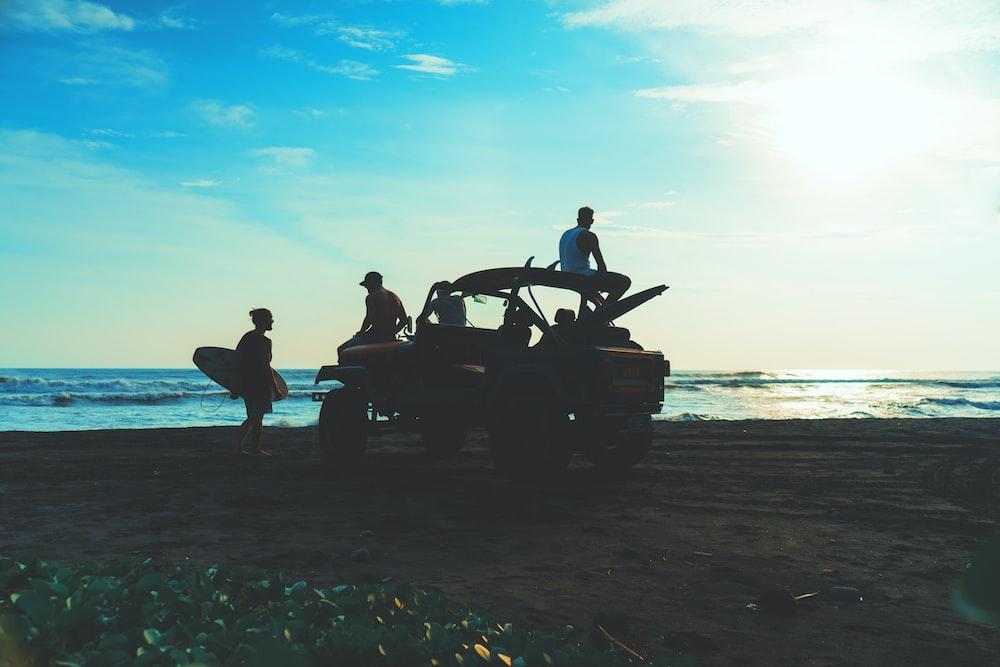 people inside truck near ocean