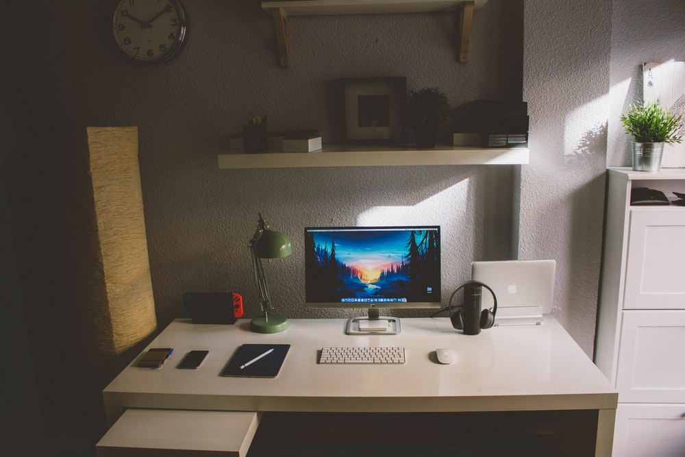 silver iMac and white cordless keyboard on white wooden table inside room