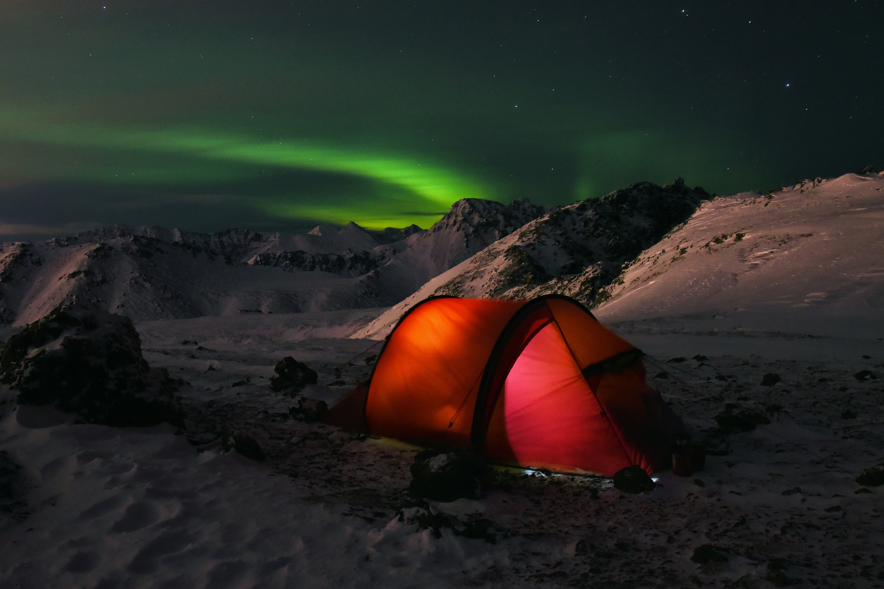 red cabin tent under aurora lights