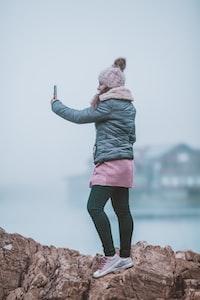 woman taking a selfie on rock