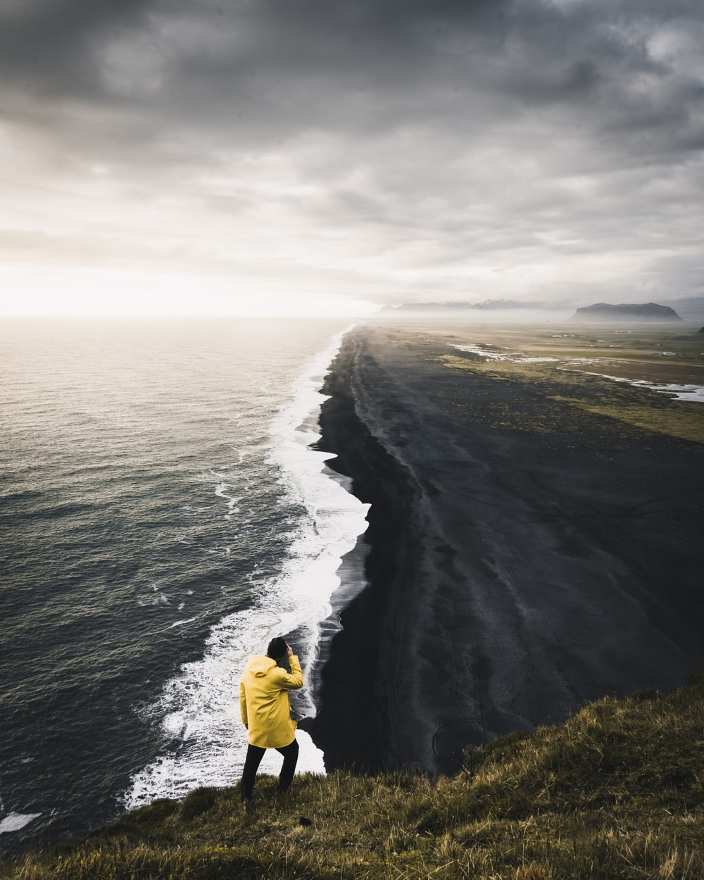 man on top hill near body of water