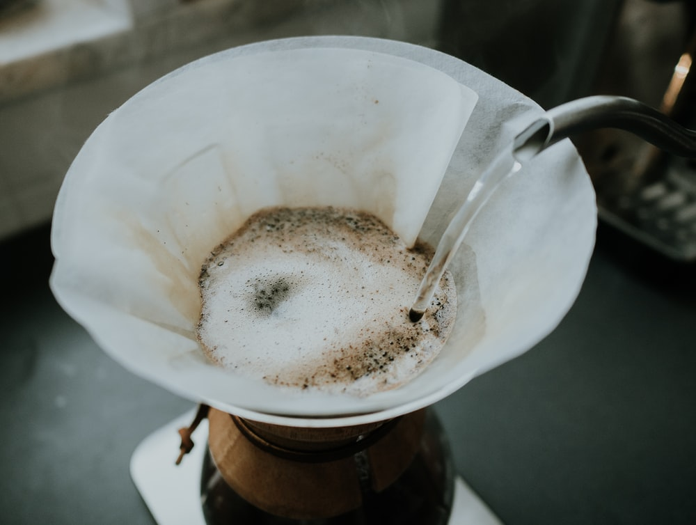 person pouring hot water on white coffee filter