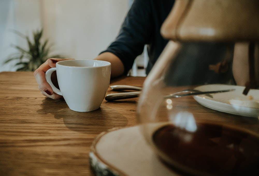white ceramic mug on brown table in white room