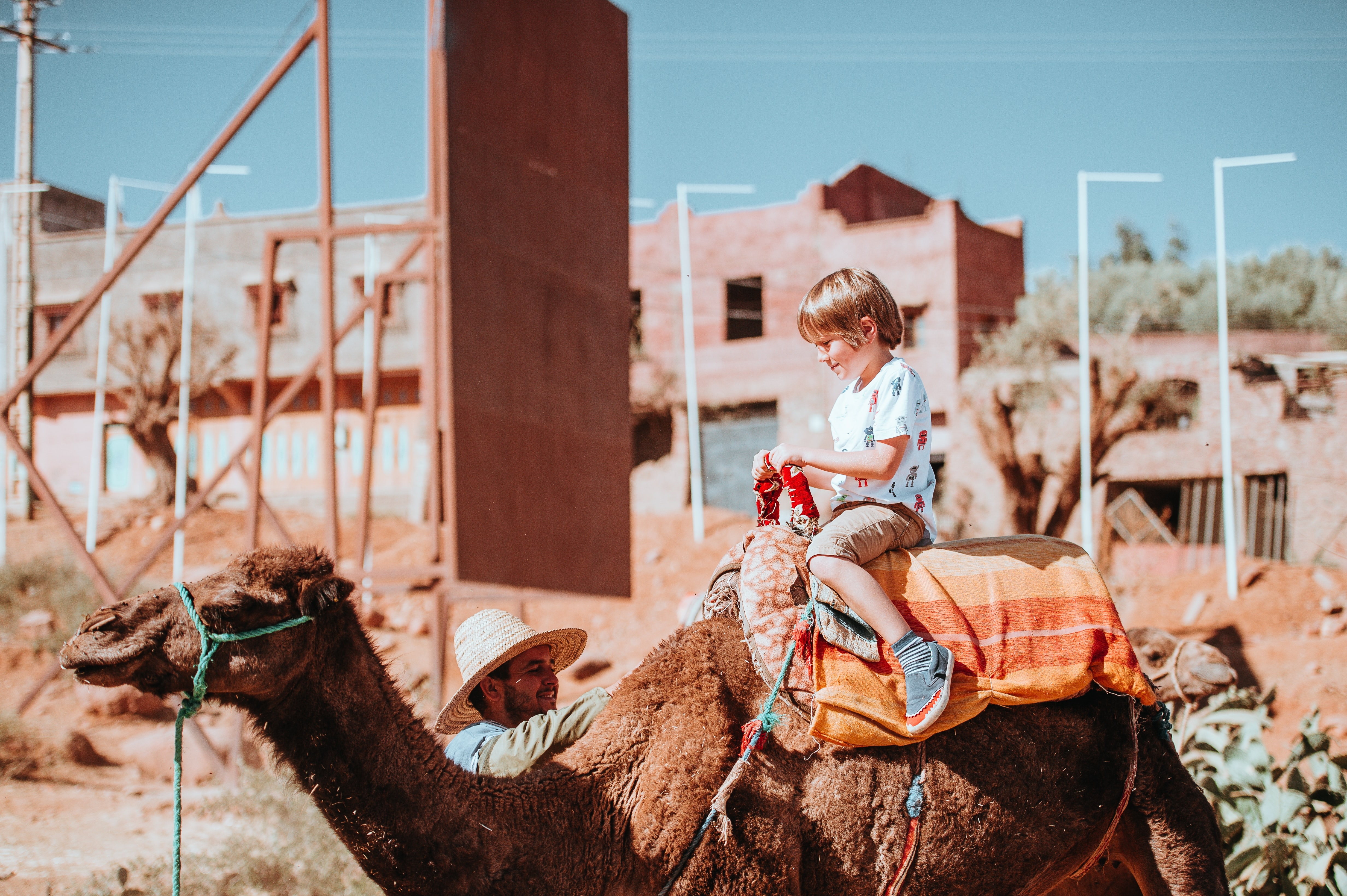 toddler riding brown camel while smiling during daytime