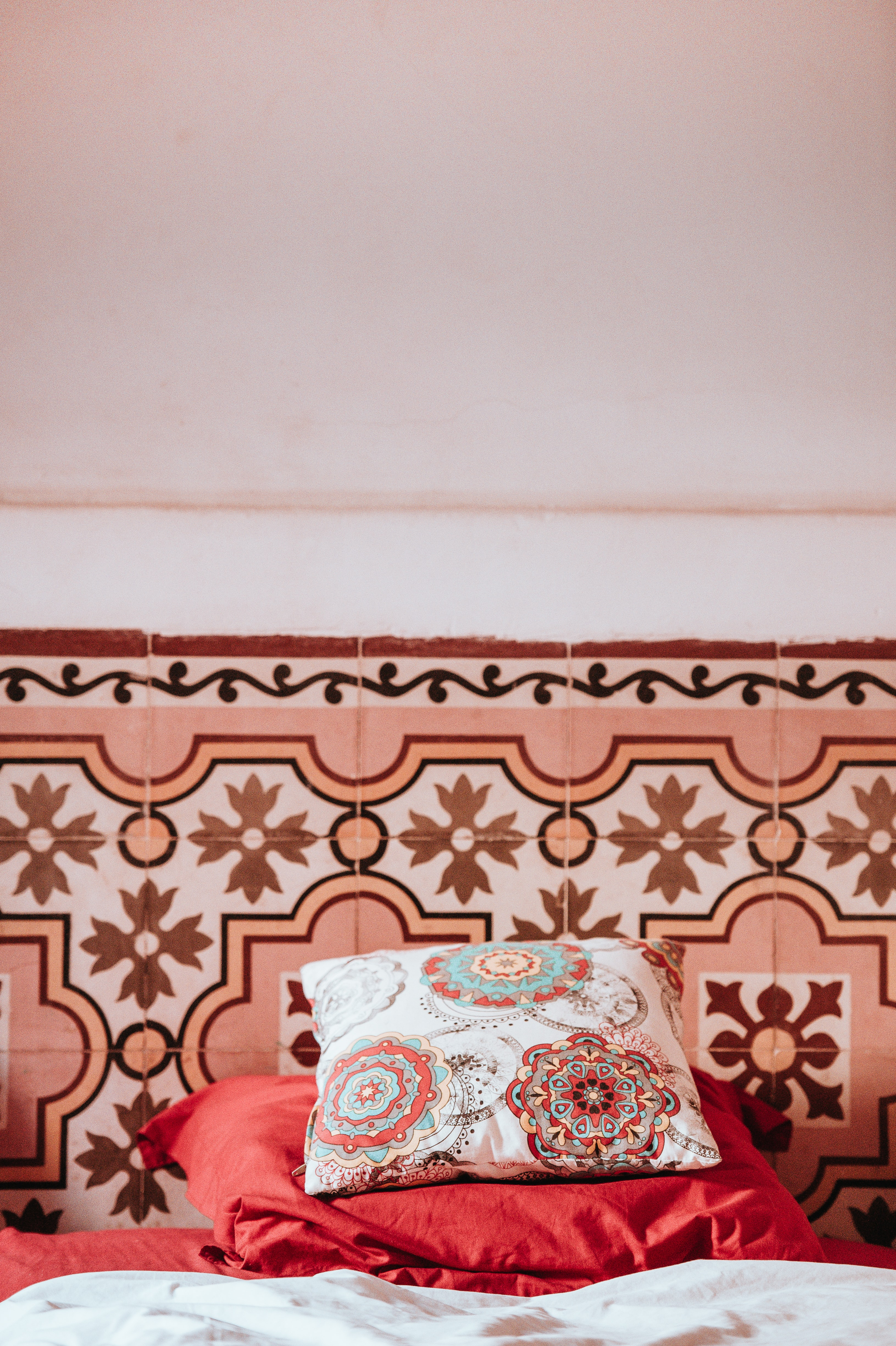 multicolored damask pillow on pink textile