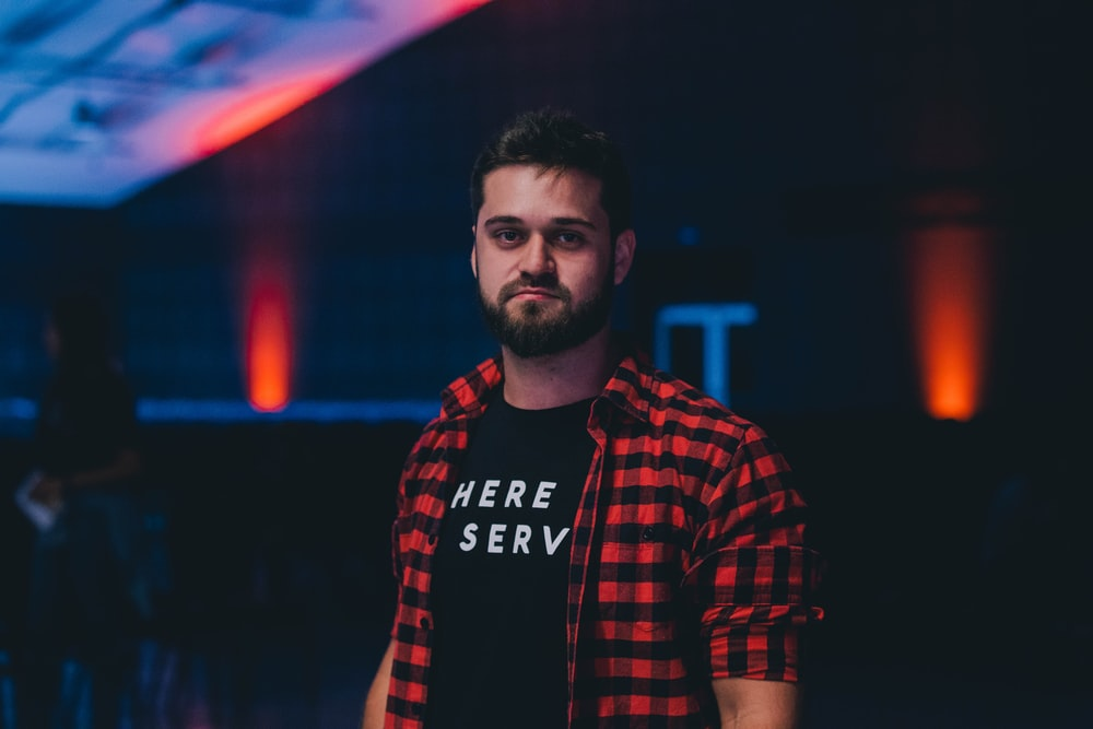 depth of field photography of man wearing black and red plaid button-up T-shirt and black shirt