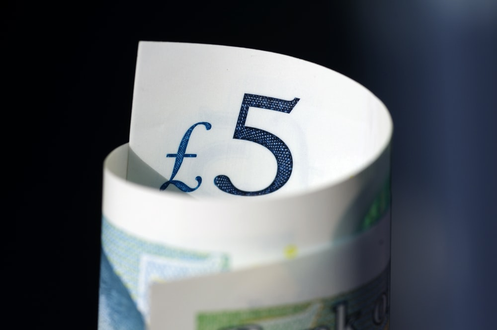 selective focus photography of rolled 5 banknote