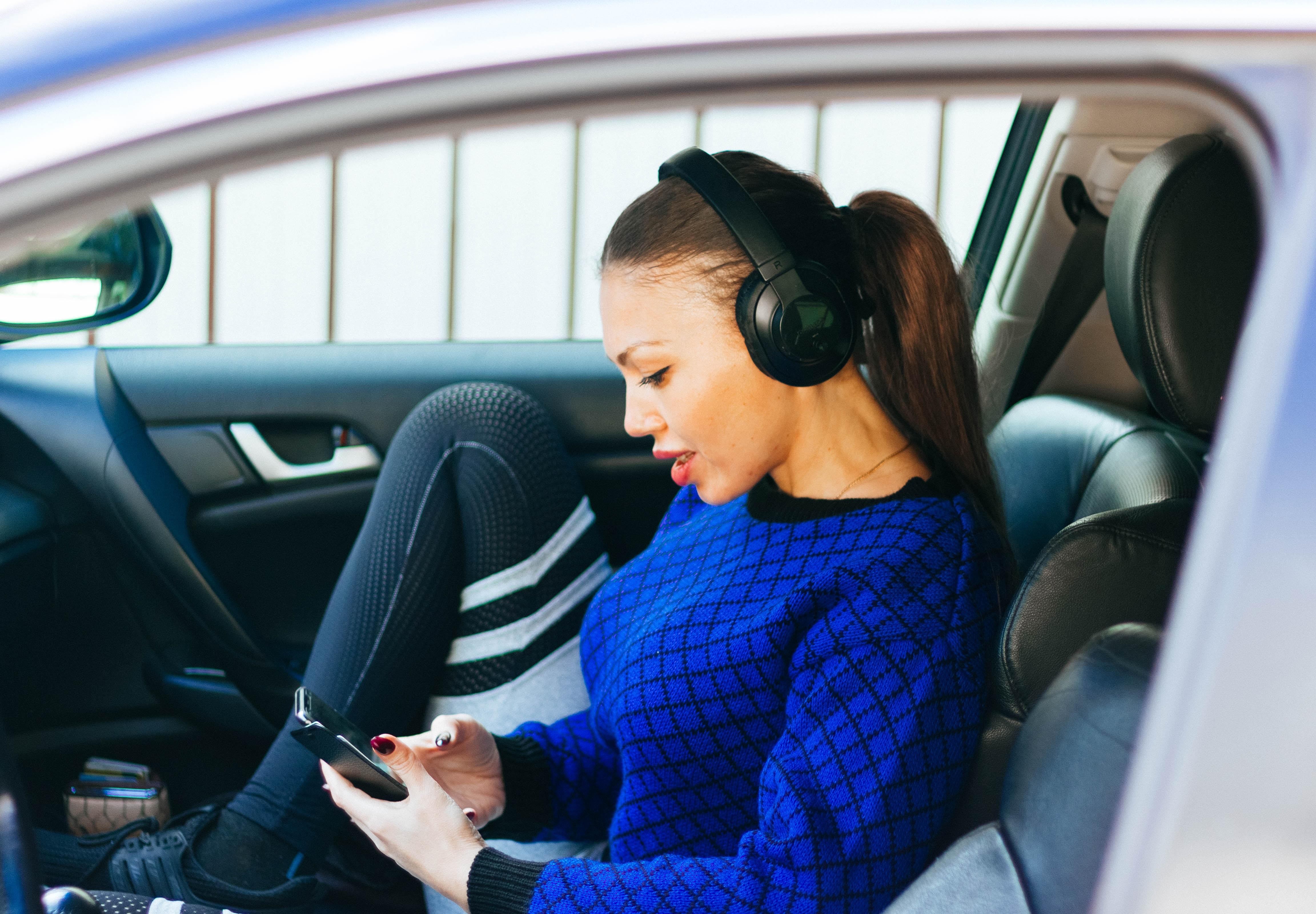 woman wearing headphones inside vehicle during daytime