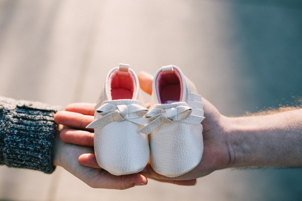 two person holding pair of baby's shoes
