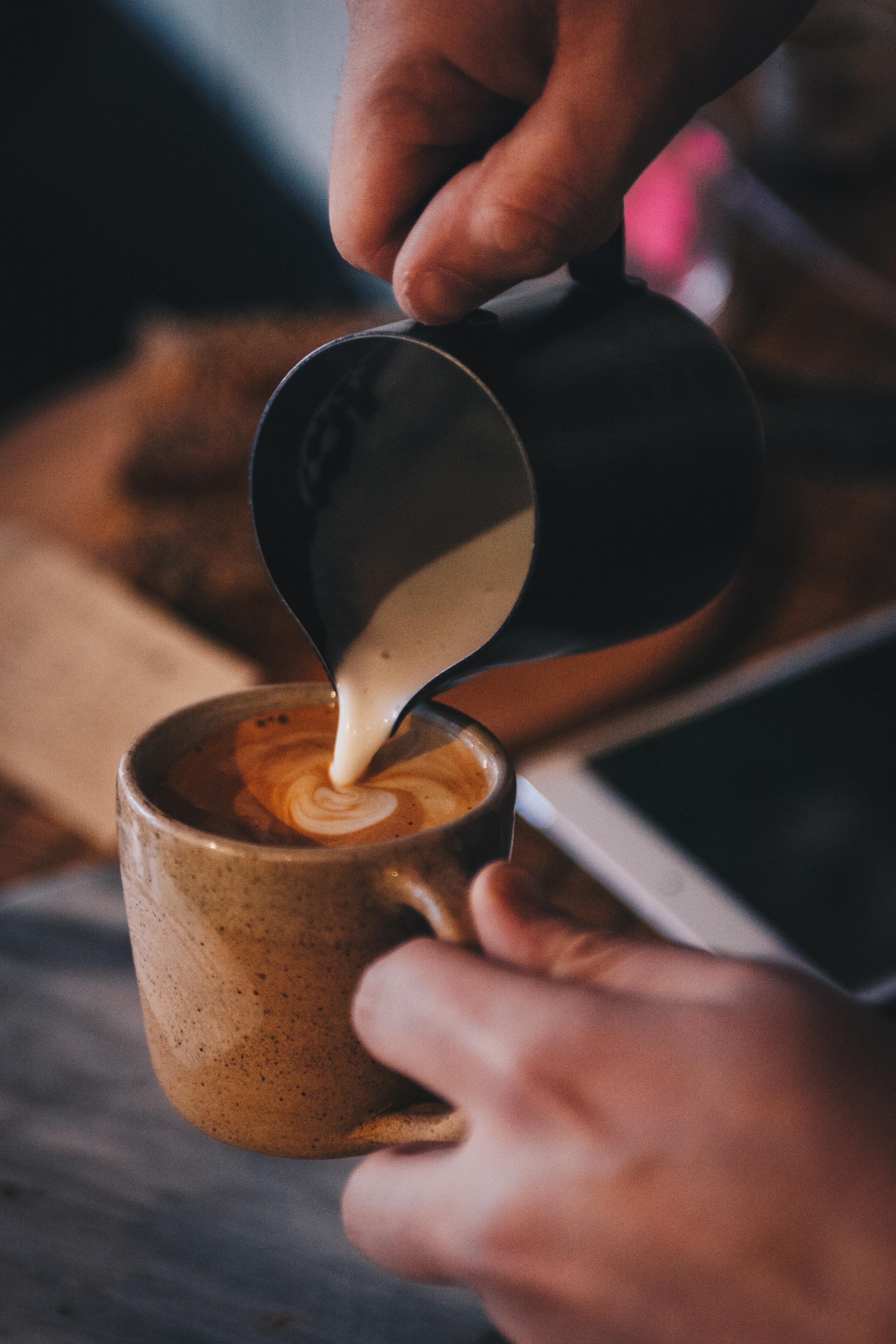 people transferring brown liquid to brown teacup