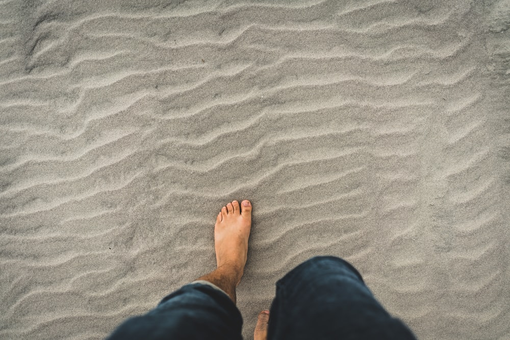 man in blue denim jeans walking through the sand