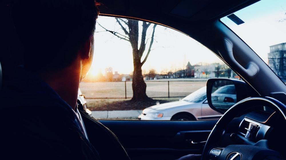 man sitting inside car looking at sun