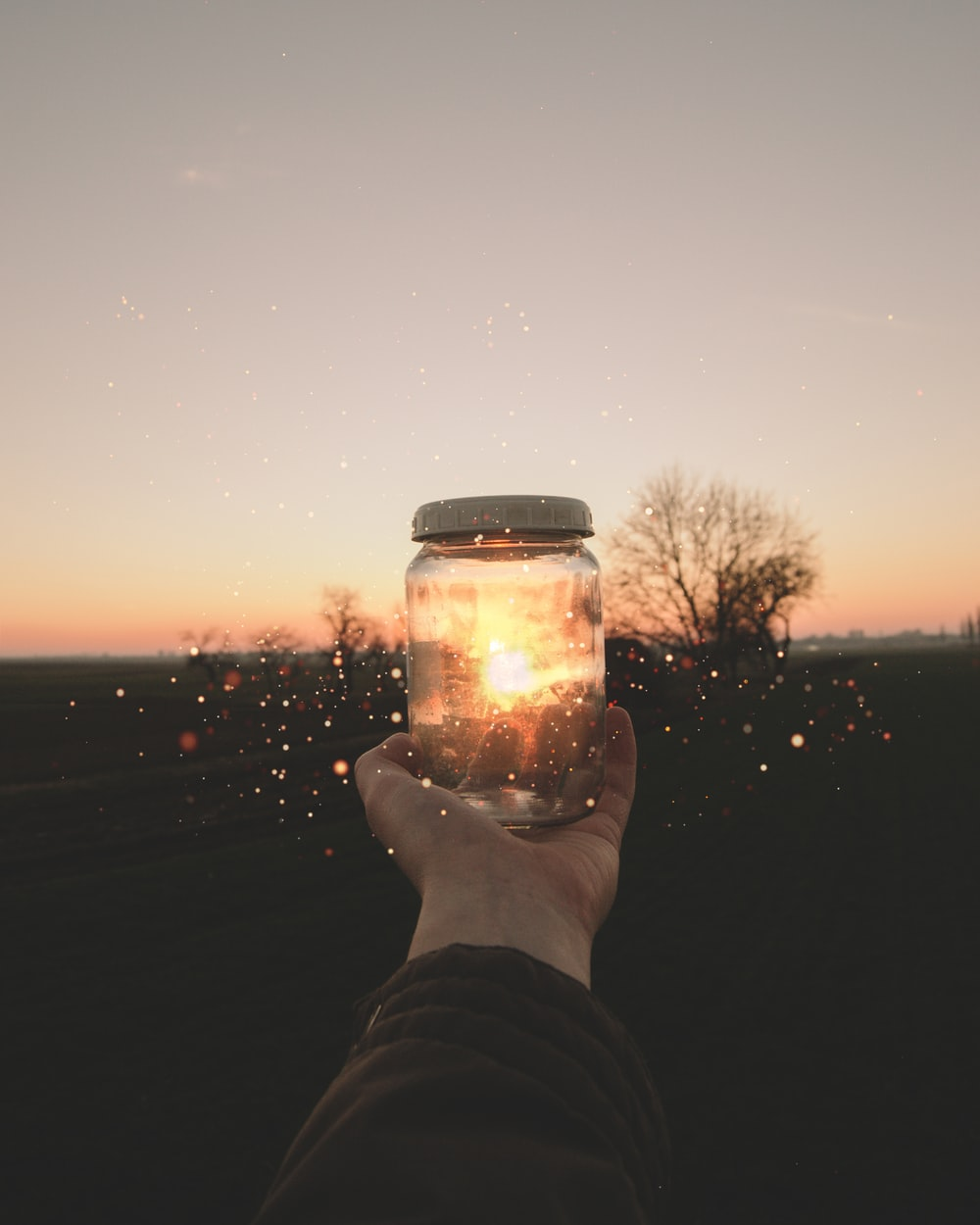 person holding glass jar