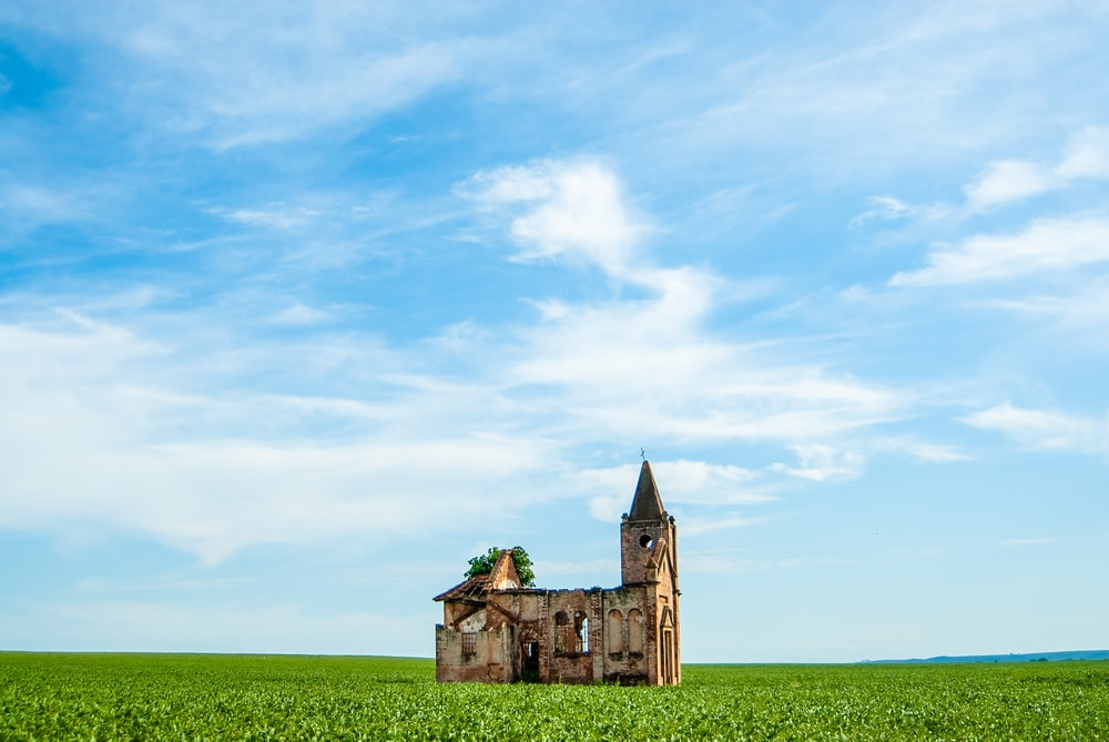 abandoned church on green grass under blue sky and white clouds during daytime