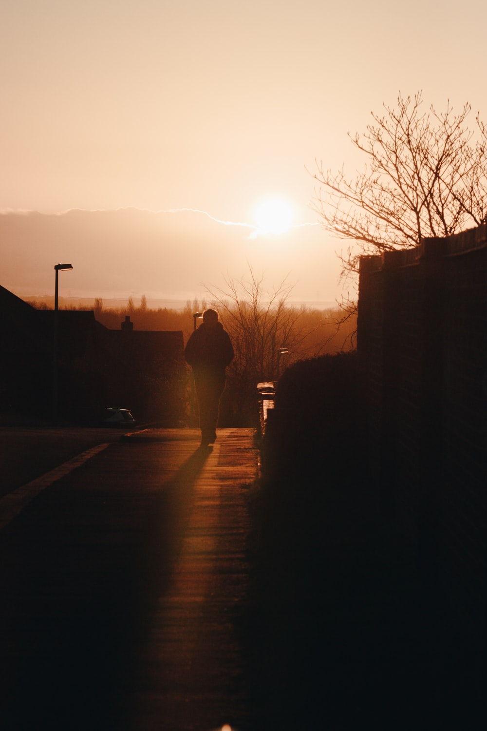 silhouette photo of man walking on street during golden hour