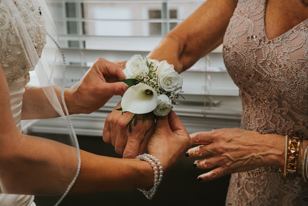 woman put white flowers on woman's hand