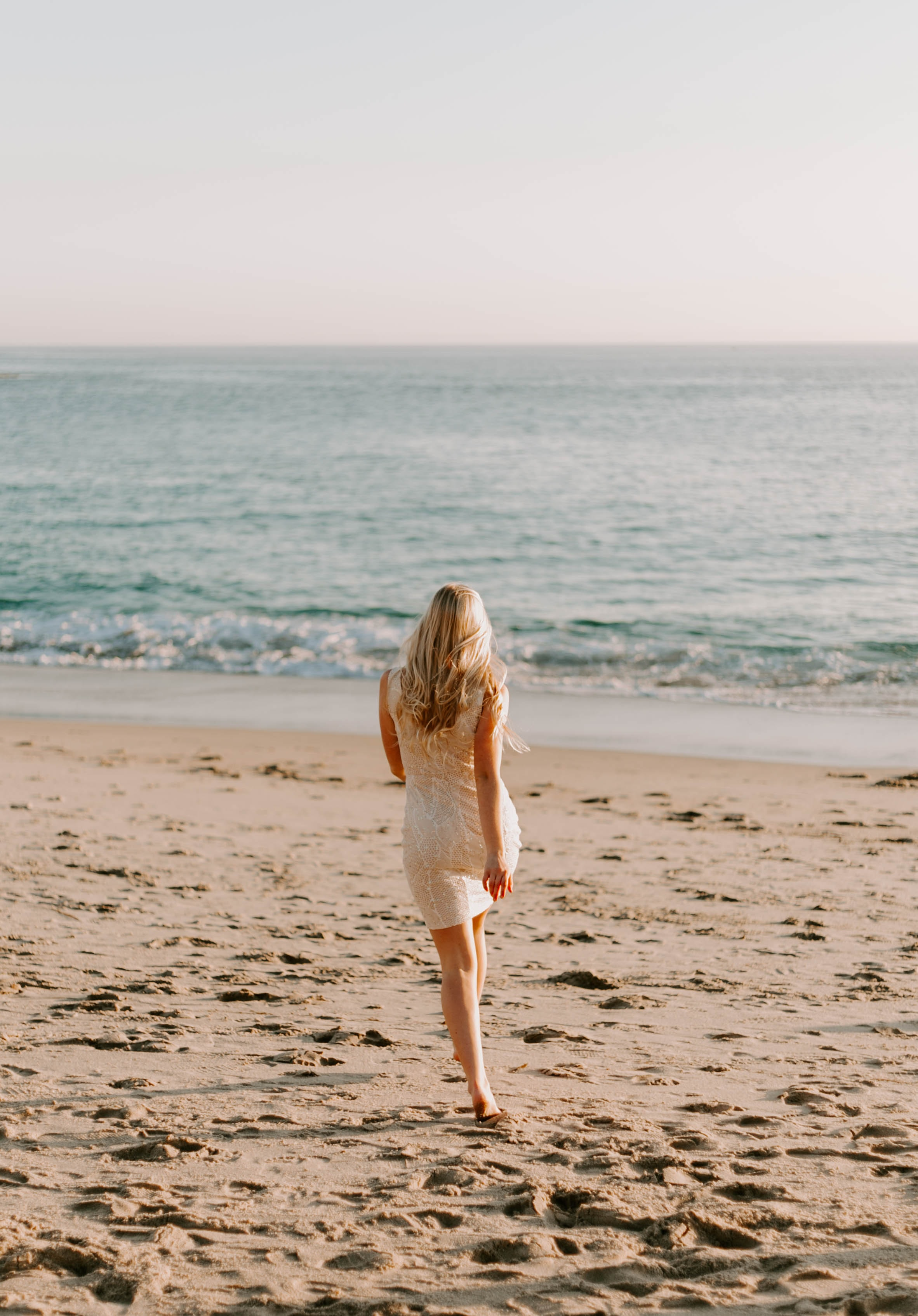 woman walking on beach overlooking sea during daytime