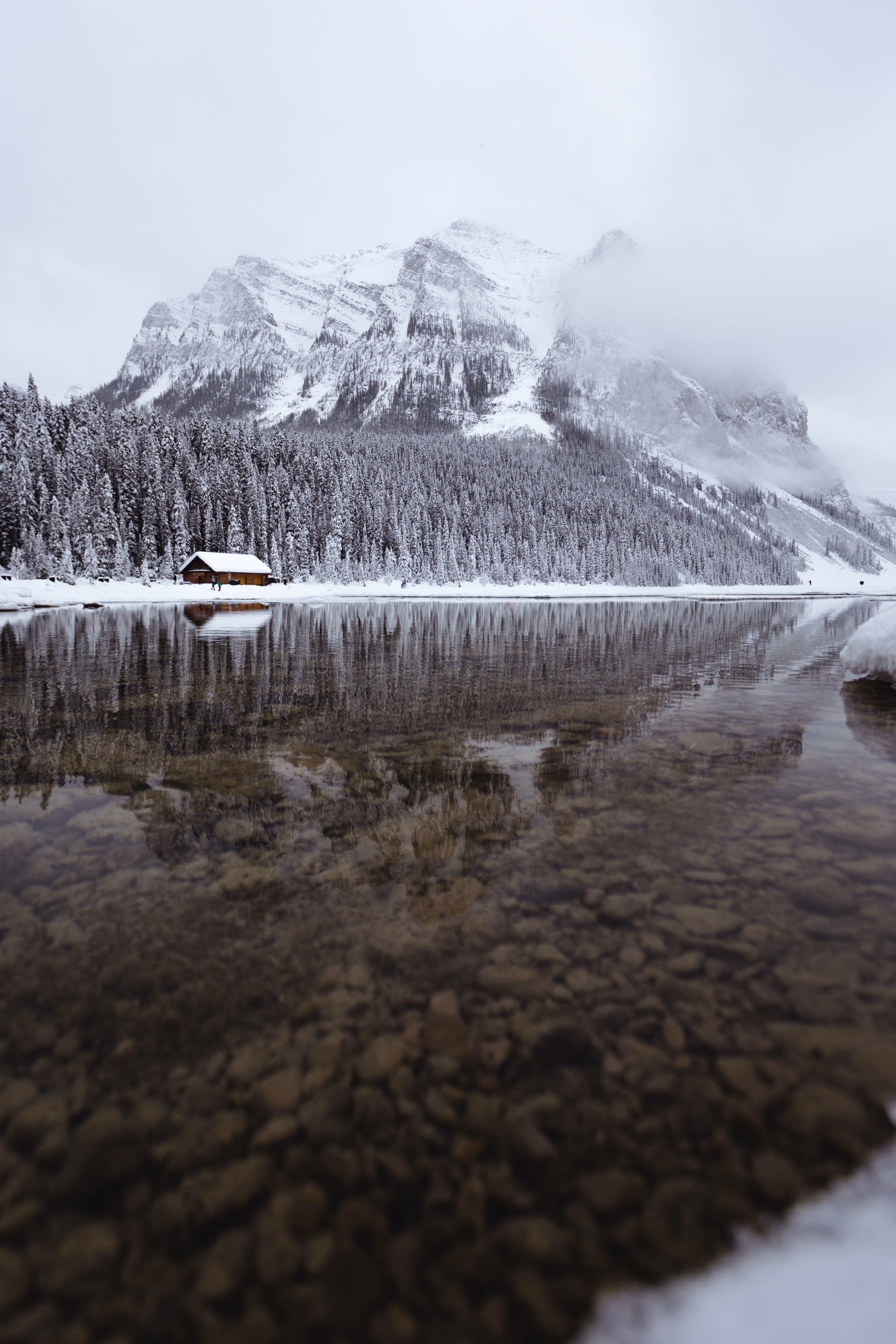 mountain covered with snow near body of water